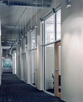 Corridor includes fifteen foot tall ceilings to radius office walls with exposed duct work and indirect lighting
