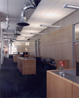 This is a picture of the open office corridor with indirect lighting, ceiling clouds and exposed duct work.