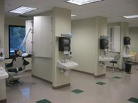 This dental lab includes dental chairs with power, water and vacuum lines for technicians use. Each dividing wall has an X-ray machine installed with laminate door covering the units.