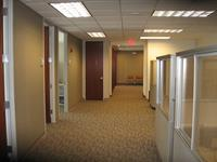 This corridor includes aluminum door frames with mahogany doors. The cubical work stations have glass panels for privacy while allowing the space to retain a spacious feel.